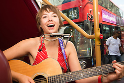 "London, July 18th 2015. Regular Southbank busker, singer/songwriter Emily Lee performs songs from her recently released EP ""Don't Forget To Love"" during the Busk in London Festival, on the Busking Bus traveling between Trafalgar Square and Marble Arch. The Fesitval aims to showcase the outstanding talents of many of the capital's finest street performers, including, musicians, acrobats, jugglers, magicians, living statues and bands."