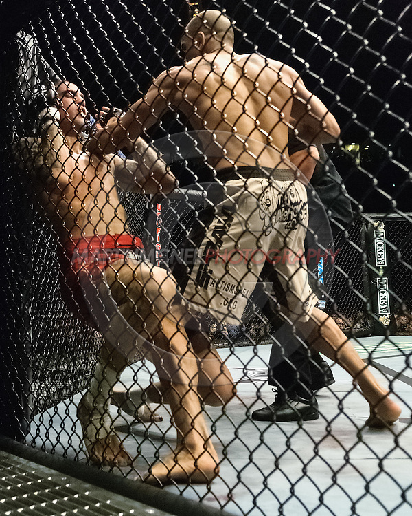 """NEWCASTLE, ENGLAND, UNITED KINGDOM, JANUARY 19 2008: Kendall Grove (left) slumps against a cage post as his knees buckle after a punch from Jorge Rivera during """"UFC 80: Rapid Fire"""" inside the Metro Radio Arena in Newcastle, England on January 19, 2008."""