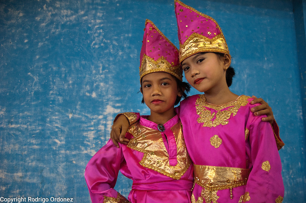 Two girls wearing traditional costumes pose for a photograph during a festival organized by children in Lubuk Basung.