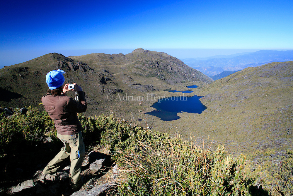 Tourist looking at Lake Chirripo from the summit of Mount Chirripo, Costa Rica's highest mountain (3820m). Chirripo National Park, Costa Rica.<br /> <br /> For pricing click on ADD TO CART (above). We accept payments via PayPal.