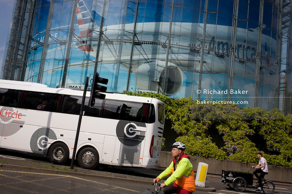 A tour coach drives beneath a large advert for American Airlines of a wide-bodied airliner in Waterloo, south London.