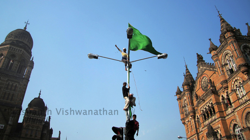 An Indian Muslim hoists flags on a lamp-post during a demonstration against U.S. President George W. Bush visit to India in Mumbai March 2, 2006.
