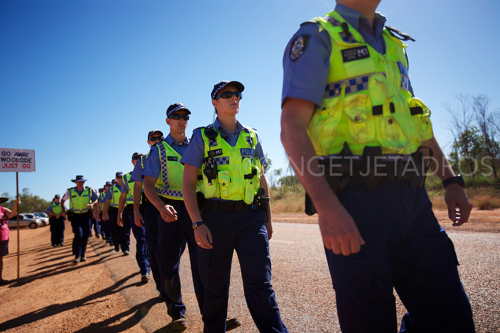 About 30 protesters have lined the road to Woodside Petroleum's proposed $30 billion gas hub at James Price Point this morning...The group met early this morning at the corner of Cape Leveque Road and Broome Highway...From 9am, a steady stream of about 25 police vehicles arrived, each carrying four or five uniformed officers...Twenty six police from the public order response team formed a line along the road to hold back protesters, while others continued to James Price Point. They were escorted by more police cars with flashing lights...Protesters lined the road as Woodside vehicles, earth moving equipment and personnel proceeded to the site...?There was 30 (protestors) and how many police here today - 100, as far as the eye could see. It?s laughable waste of taxpayers? money.?..Broome, Western Australia, 2012.©Ingetje Tadros.www.ingetjetadros.com