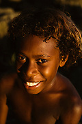 A young Ni-Vanuatu boy sits for a sunset lit portrait near the coast of Tanna island.