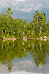 Trees and Mount Katahdin reflect in the still waters of Katahdin Lake in Maine's Baxter State Park.