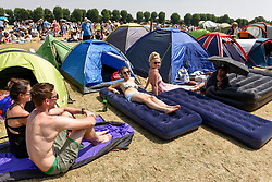 © Licensed to London News Pictures. 06/07/2018. LONDON, UK. Spectators sunbathe whilst queuing for day tickets in Wimbledon Park to the Wimbledon Tennis Championships.  Temperatures forecast to approach 30C mean that the majority have taken precautions to protect themselves from the sun by wearing sunglasses and sunhats.  Photo credit: Stephen Chung/LNP