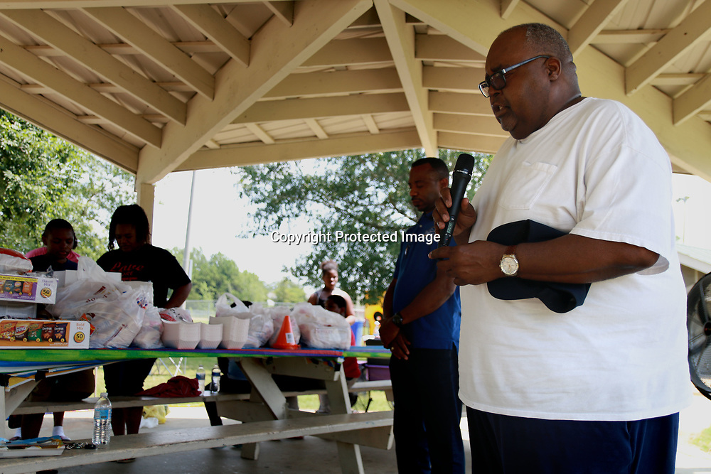 White Hill Baptist Church Deacon Daniel Jenkins leads community members in a moment of prayer the Love More Hate Never community gathering at Theron Nickols park Saturday.