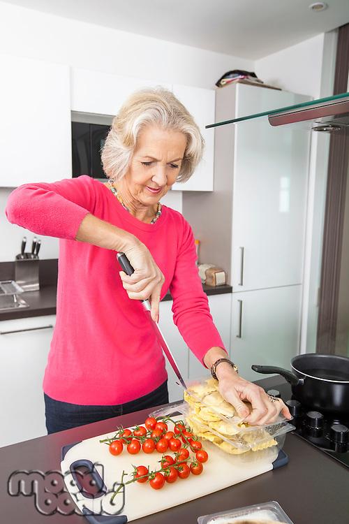 Senior woman preparing food at kitchen counter