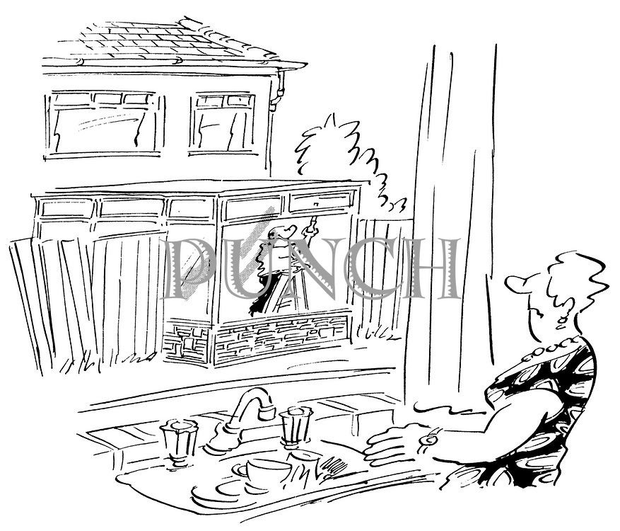 (A woman looking out of her kitchen window at a man building an extension to his house that has broken through the fence into her back garden)