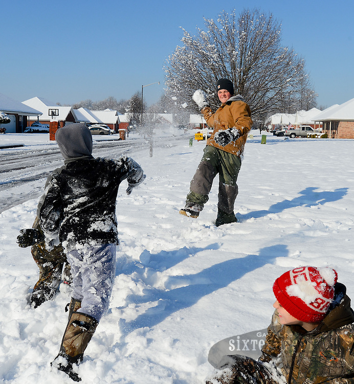 Gary Cosby Jr./Decatur Daily   Snow blankets the Tennessee Valley Thursday morning after a snow that began late Wednesday and fell through much of the night.  Eli Terry, left, zings a snowball at Colin Springer as they play in Hartselle.