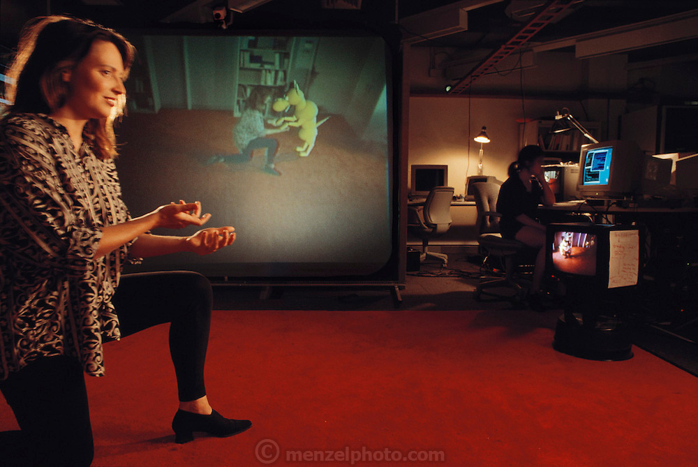 "Pattie Maes (and grad student Cecil). Maes is photographed with ""ALIVE,"" a real-time virtual reality system.  She captioned the photo:  ""A novel system developed at the MIT Media Lab makes it possible for a person to interact with artificial creatures such as this dog using natural gestures."""