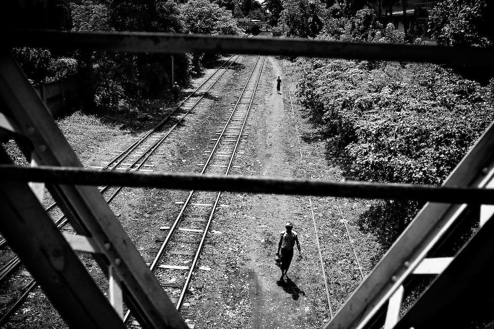 Men walk the railroad tracks in Yangon, Myanmar.