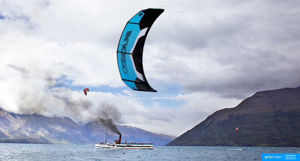 Kite surfers make the most of favourable wind conditions on Lake Wakatipu, Queenstown as local tourist attraction The TSS Earnslaw, a 1912 Edwardian vintage twin screw steam boat sails past on it's return from Walter Peak Station. Queenstown. South Island, New Zealand. 17th November, 2011