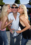 NEW YORK - MAY 29:  David Lee Roth poses with models at Jason Binn's Hamptons Magazine Memorial Day Weekend Party at his private home May 29, 2004 in New York City.   (Photo by Matthew Peyton)