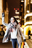 Portrait of young attractive woman standing while calling for taxi after night shopping