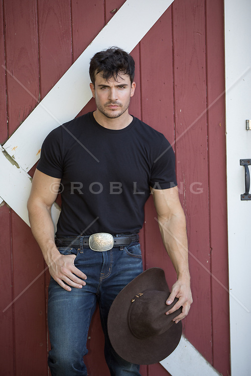 hot cowboy leaning against a barn