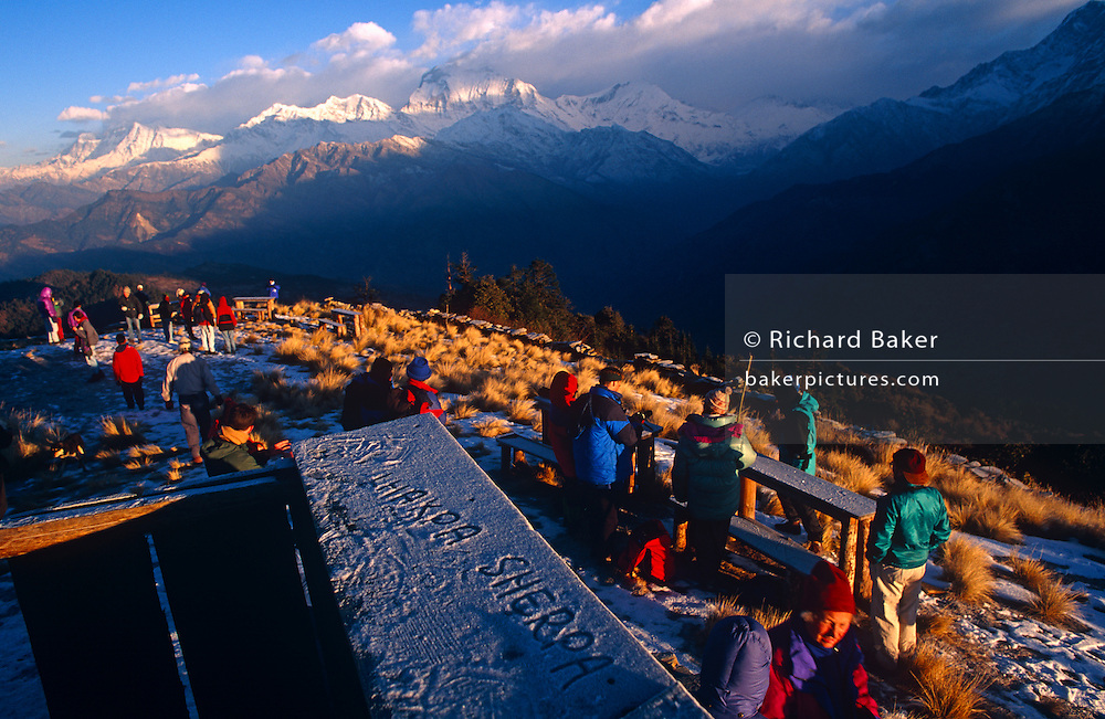 High in the Himalayan foothills, dawn arrives on a bitterly cold morning at Poon Hill. Trekkers have gathered at this spot to take in the wonder of this spectacular landscape of snow-capped peaks in the distance. A sherpa has written his name in ice on a rail and western travellers continue their journey higher into the Annapurna range to sample the inner-peace to be discovered here in one of the most dramatic locations on the planet. Villages partly-depend on the agriculture of rice-growing and also on the passing tourist trade. Western trekkers walk through tiny communities on their way up the series of climbing trails of the Annapurna Conservation Sanctuary circuit, a rigorous walk from the low hills of Pokhara to the higher altitudes of Annapurna, the (26,000 feet (8,000 metre) peak.