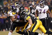 Lawrence Timmons (94), James Harrison (92) and James Farrior (51) of the Pittsburgh Steelers make a stop against Willis McGahee of the Baltimore Ravens in the AFC Divisional Playoff game on Jan. 15, 2011 at Heinz Field in Pittsburgh, Pennsylvania. The Steelers won 31-24. (Photo by Joe Robbins)