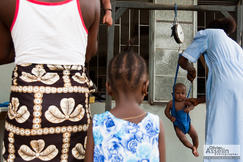 MCH aide Aminata Koroma (right) weights a child at the Pujehun Government hospital in Pujehun, Sierra Leone on Friday March 19, 2010..
