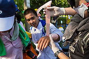 01 DECEMBER 2013 - BANGKOK, THAILAND: Thai medics help a man injured during an anti-government riot in Bangkok. Thousands of anti-government Thais confronted riot police at Phanitchayakan Intersection, where Rama V and Phitsanoluk Roads intersect, next to Government House (the office of the Prime Minister). Protestors threw rocks, cherry bombs, small explosives and Molotov cocktails at police who responded with waves of tear gas and chemical dispersal weapons. At least four people were killed at a university in suburban Bangkok when gangs of pro-government and anti-government demonstrators clashed. This is the most serious political violence in Thailand since 2010.    PHOTO BY JACK KURTZ