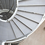 Curved grey winding office stairs with man.