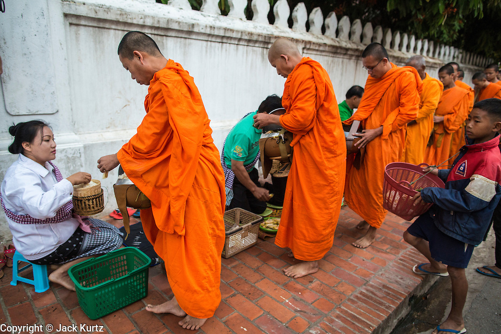 """11 MARCH 2013 - LUANG PRABANG, LAOS:  Buddhist monks collect alms during the tak bat in Luang Prabang. The """"Tak Bat"""" is a daily ritual in most of Laos (and other Theravada Buddhist countries like Thailand and Cambodia). Monks leave their temples at dawn and walk silently through the streets and people put rice and other foodstuffs into their alms bowls. Luang Prabang, in northern Laos, is particularly well known for the morning """"tak bat"""" because of the large number temples and monks in the city. Most mornings hundreds of monks go out to collect alms from people.   PHOTO BY JACK KURTZ"""
