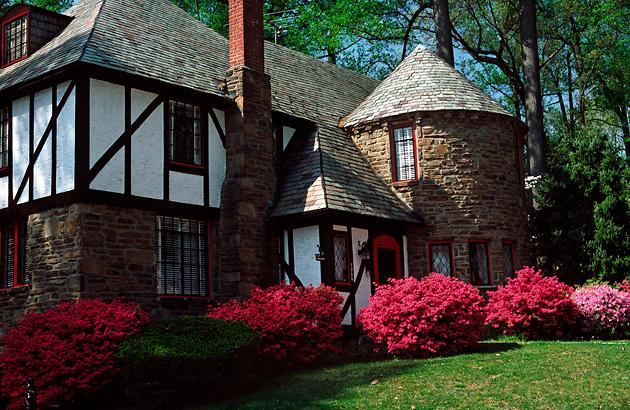 Tudor house, round turret; stone; stucco; colorful azaleas; spring; PR