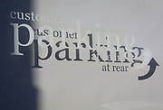 A detail of sign lettering and shadows telling cusomers of a local business that customer parking is at the rear of the premises, on 7th November 2019, in Surbiton, London, England