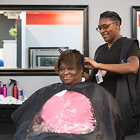 Student Asia Rosebud straightens Tesha Watkins' hair Thursday night during the free haircut night at the Tupelo Academy of Cosmetology. Each week, the school offers free hair services from 12 p.m. to 2:30 p.m. on Wednesdays, and 5:30 p.m. to 8:30 p.m. on Thursday nights.