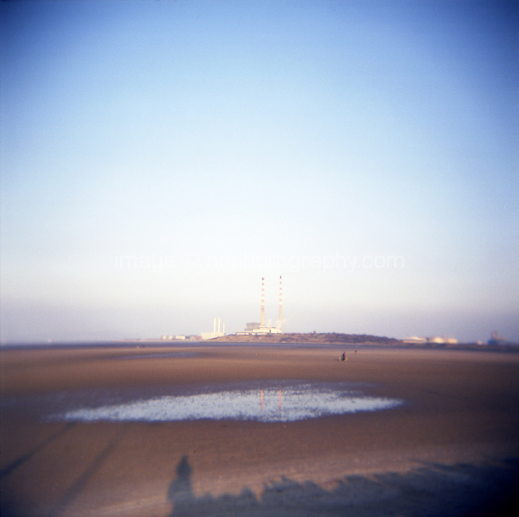 View of ringsend power station from Sandymount strand at low tide in Dublin Ireland