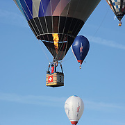 Stefan Zeberli, Switzerland, (three) and other hot air balloons in the skies around rural Michigan near Battle Creek as they reach a target area during competition in the 20th FAI World Hot Air Ballooning Championships. Battle Creek, Michigan, USA. 22nd August 2012. Photo Tim Clayton