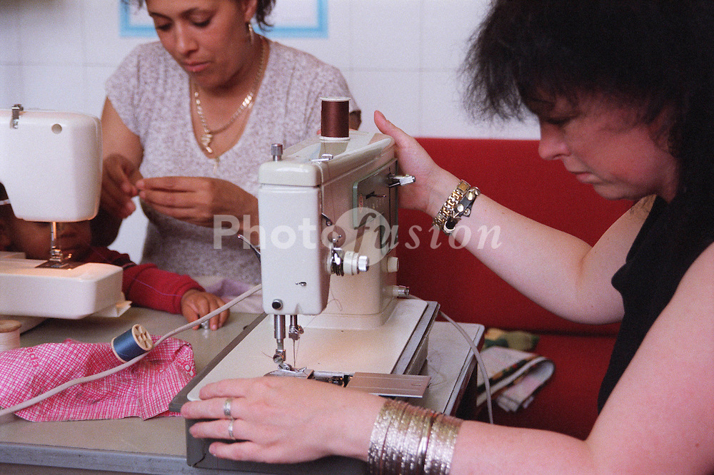 Parent volunteers of primary school pupils using sewing machines to make cushion covers,