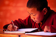 A young monk takes an exam at the Shree Mahakaruna Sakyapa School in lo Manthang, Upper Mustang, Nepal.