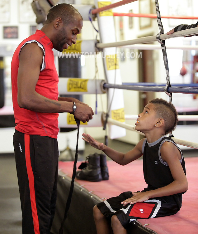 Terrence Thomas gets ready to tape the hands his son Terrence Thomas II, an 8-year-old boxer,  at the Newburgh Boxing Club on Wednesday, Aug. 8, 2012.