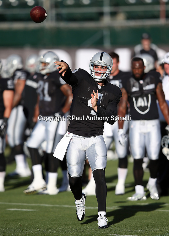 Oakland Raiders quarterback Derek Carr (4) throws a pregame pass before the 2014 NFL preseason football game against the Detroit Lions on Friday, Aug. 15, 2014 in Oakland, Calif. The Raiders won the game 27-26. ©Paul Anthony Spinelli
