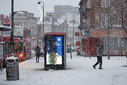© Licensed to London News Pictures. 10/12/2017. London, UK. People commute on Wood Green High Street in north London during a heavy snowfall on Sunday, 10 December 2017. Photo credit: Tolga Akmen/LNP