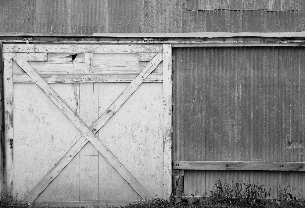 Weathered barn door contrasts with corrugated metal siding.