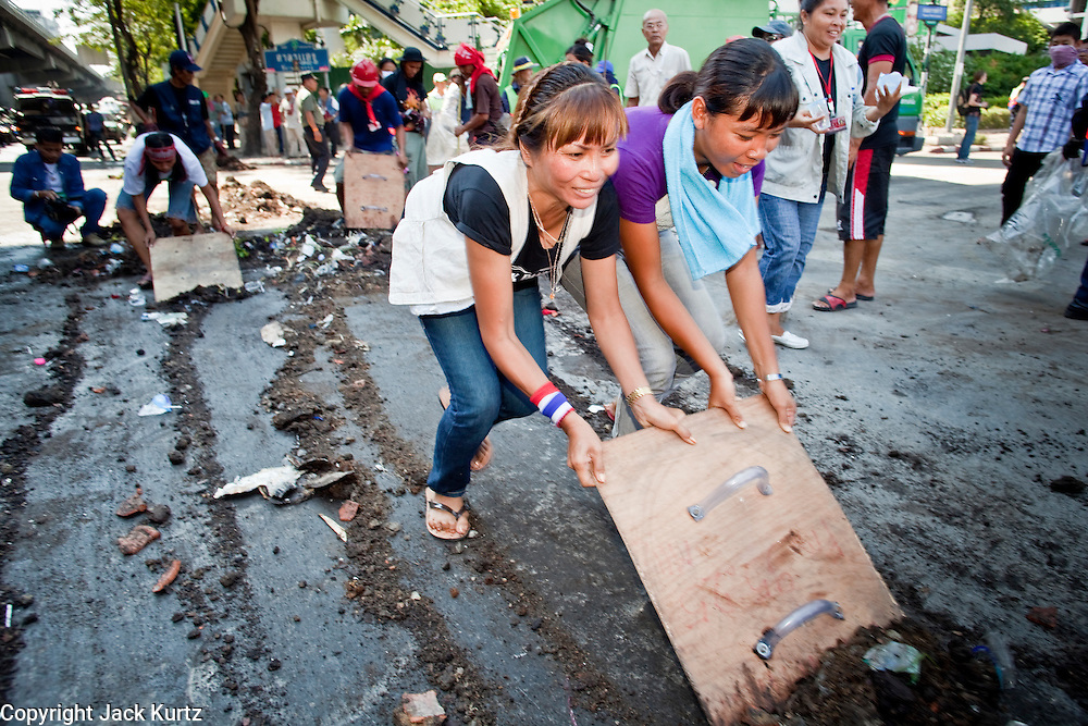 Apr. 30 - BANGKOK, THAILAND:  Red Shirt women use one of their home made shields to clean up diesel fuel soaked dirt after they tore down one of their barricades in Bangkok Friday. The Red Shirts moved one of their barricades in the Sala Daeng Intersection in Bangkok Friday In one of the first positive moves to take place since the Red Shirts occupied central Bangkok in early April. The barricade was moved far enough back to open one lane of traffic on  Ratchadamri Street to allow ambulance access to King Chulalongkorn Memorial Hospital, a large hospital at the intersection. Many of the patients in the hospital have been moved to other hospitals because a group of Red Shirts entered the hospital Thursday looking for Thai security personnel, who were not in the hospital. The stand off between the Red Shirts and the government enters its third month in May. The Red Shirts continue to call for Thai Prime Minister Abhisit Vejjajiva to step down and dissolve parliament and demand the return of ousted Prime Minister Thaksin Shinawatra.   PHOTO BY JACK KURTZ