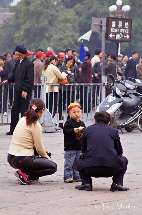CHINA, BEIJING:  Chinese parents squat down to talk to their ice-cream eating son as crowds of tourists wait in line at the entrance to The Forbidden City in Beijing.