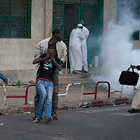 A child is rescued after suffering from the impact of a lacrymogene bomb in central Dakar, Senegal Friday, Feb. 17, 2012..Anti-government protesters and police clashed for a third consecutive day Friday, engaging in running street battles of rock throwing and tear gas in the streets of Dakar's downtown Plateau neighborhood. Demonstrators are defying a government ban on protests to call for the departure of 85-year-old President Abdoulaye Wade, who is running for a third term in next week's election..COPYRIGHT:Sylvain Cherkaoui