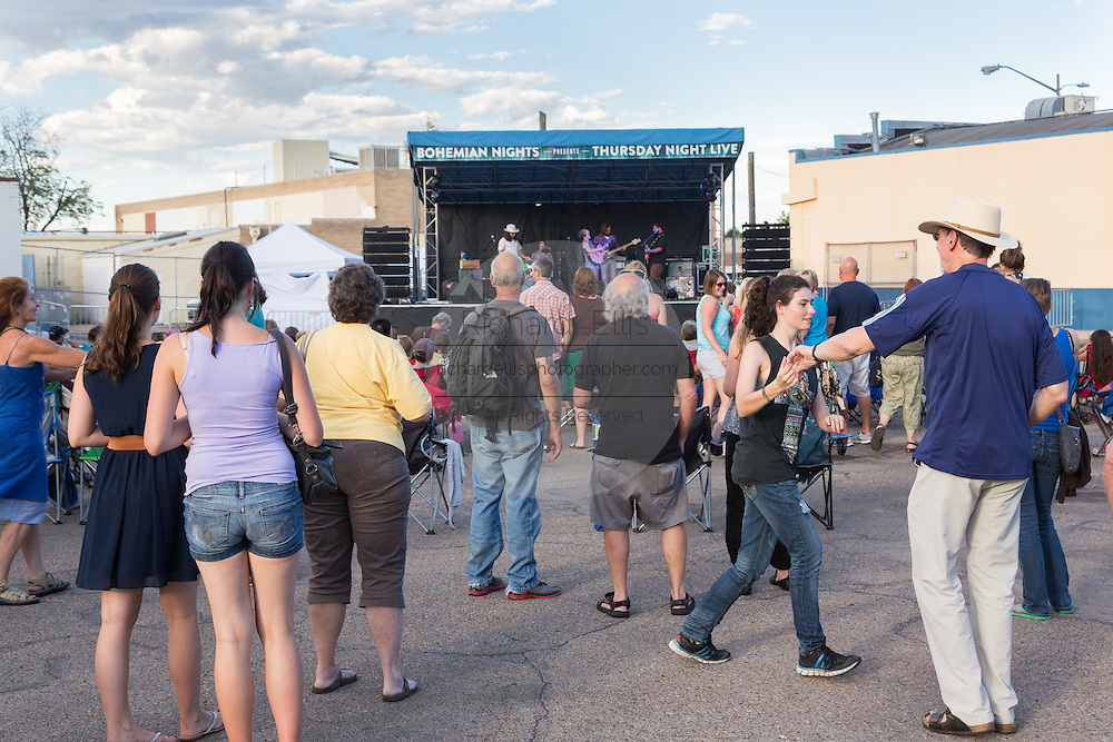 People dance and gather to listen to a free concert during Bohemian Nights on Thursdays in the Old Town historic shopping and restaurant district in Fort Collins, Colorado.
