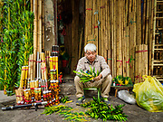 "24 DECEMBER 2017 - HANOI, VIETNAM: A man trims bamboo is shop in the old quarter of Hanoi. The old quarter is the heart of Hanoi, with narrow streets and lots of small shops but it's being ""gentrified"" because of tourism and some of the shops are being turned into hotels and cafes for tourists and wealthy Vietnamese.           PHOTO BY JACK KURTZ"