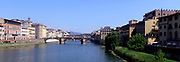 Distant photo of the Ponte Vecchio or 'Old Bridge', a Medieval stone bridge over the Arno River in Florence, Italy. It is a closed-spandrel segmental arch bridge. The bridge is famous for having shops built along it, originally butchers, but now souvenir shops, jewellers, and art dealers reside in the shops.