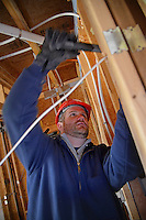 NC State volunteer hammers while working on the Build-A-Block Habitat for Humanity project.