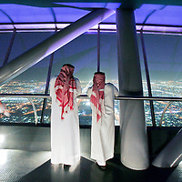 Saudi men look out over the city from the top of the Kingdom Tower in Riyadh. April 2007.