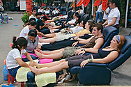Tourists receiving foot massage on streets on Chiang Mai, Thailand.