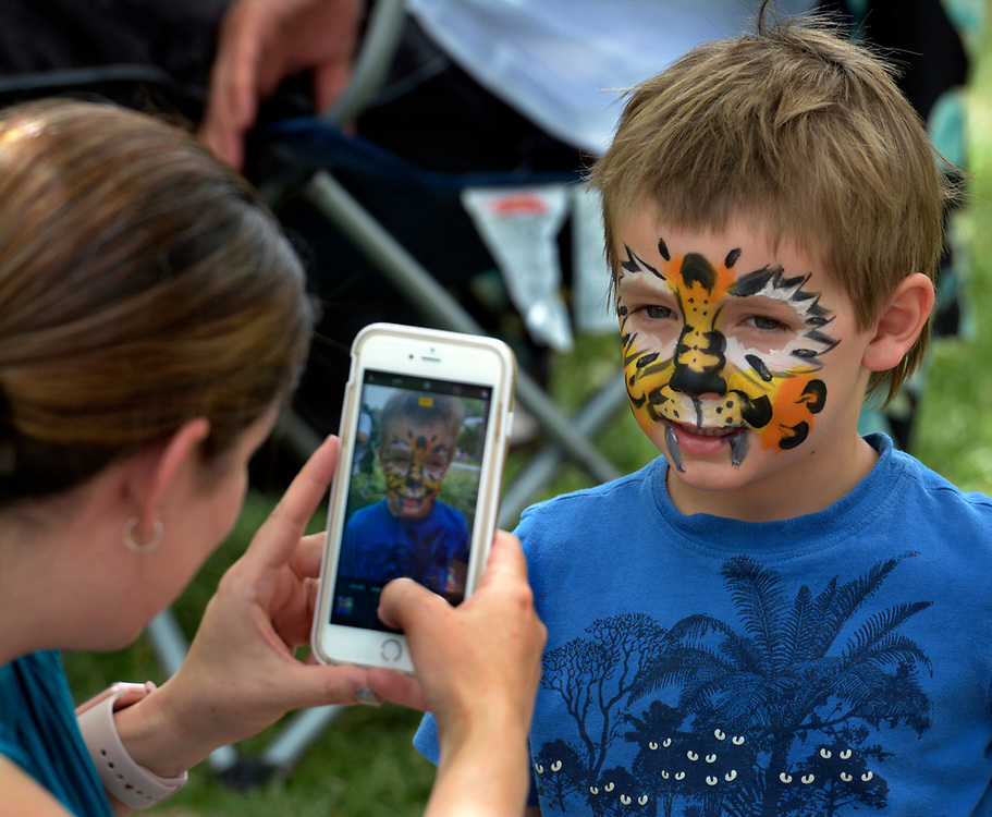 gbs051417j/ASEC -- Amanda Enghauser of Albuquerque takes a photo of her son Ian, 5, face painted as a cheetah, during the Mother's Day Concert at the Zoo on Sunday, May 14, 2017. The event also had Zoo Mom's Discovery Stations,  special ape activities for Missing Orangutan Mothers (MOM) and a World Animal Encounters Show.(Greg Sorber/Albuquerque Journal)