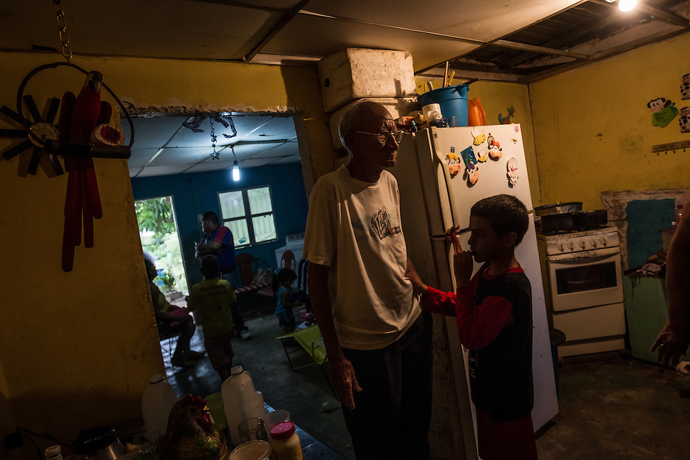 "MENE GRANDE, VENEZUELA - AUGUST 27, 2014: A man struggling to make ends meet walks into the kitchen of his home located a short distance from Zumaque 1 oil well, considered the first successful oil well in Venezuela, that was discovered 100 years ago. Despite being so close to this  landmark well, the streets are unpaved and people live in shacks made from corrugated metal sheets. ""Look at the riches of Venezuela,"" said Ramón Materán, 64, a laborer. ""For all of Venezuela's riches things are pretty neglected here."" PHOTO: Meridith Kohut for The New York Times"