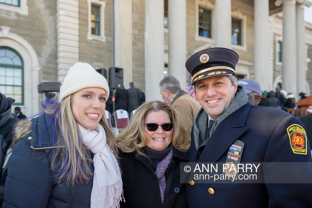 Mineola, New York, USA. January 1, 2018. L-R, SUE MOLLER, who was 2017 candidate for Hempstead Town Council, EILEEN NAPOLITANO, who was candidate for Nassau County Legislature, and member of North Bellmore Fire Department pose for photo after historic outdoor swearing-In of LAURA CURRAN as Nassau County Executive, the first female County Executive. Temperature was a freezing 14 ℉ Fahrenheit / -10 ℃  Celsius for the outdoor ceremony held in front of Theodore Roosevelt Executive & Legislative Building.