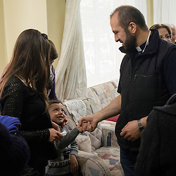 After a mass celebrated at a home, Father Adday greets a child. <br /> Father Adday travels at least once a week to different parts of Turkey visiting the community of Iraqi Christian refugees. The exact number is unknown but it is estimated to be 40,000.